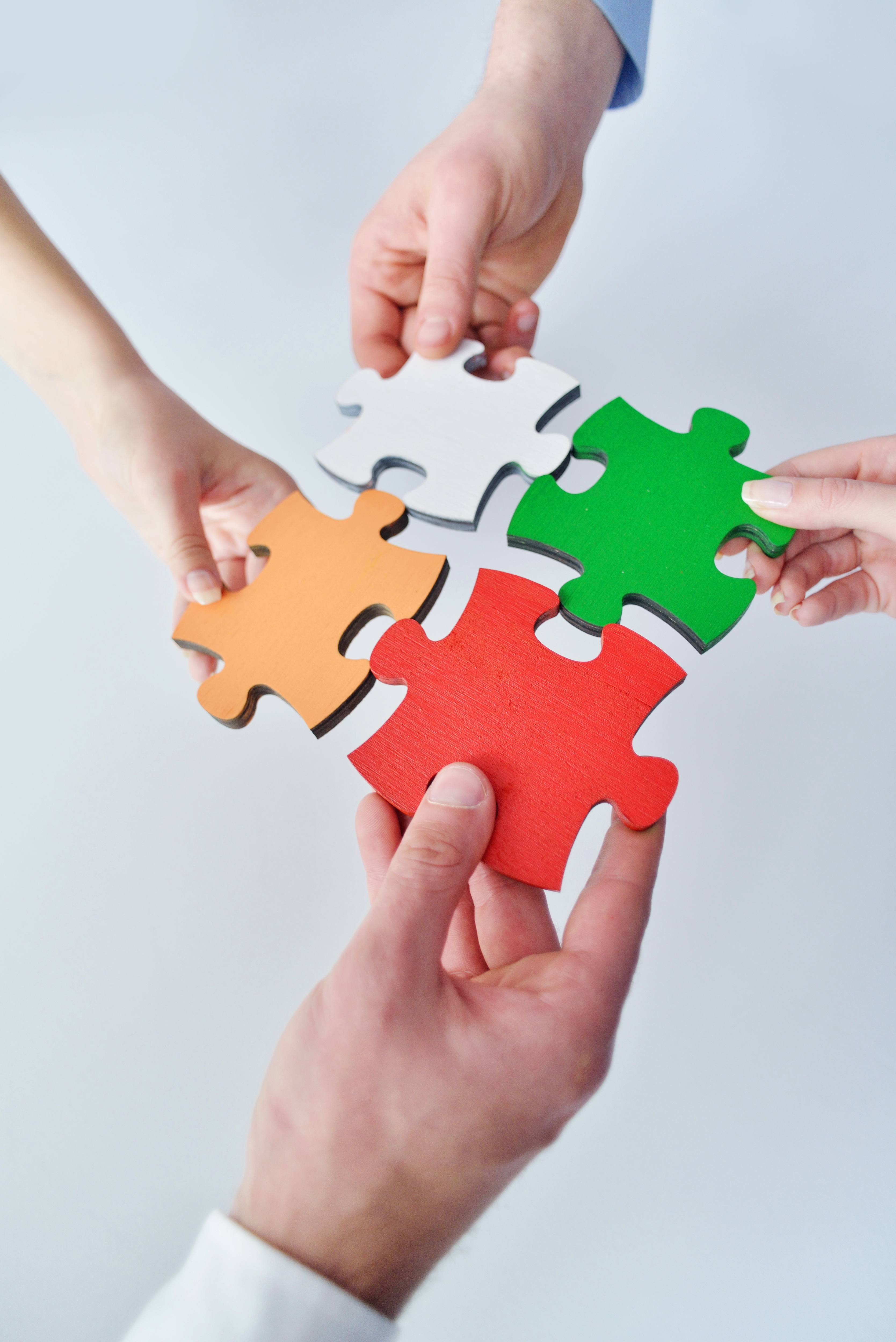 Group of business people assembling jigsaw puzzle and represent team s