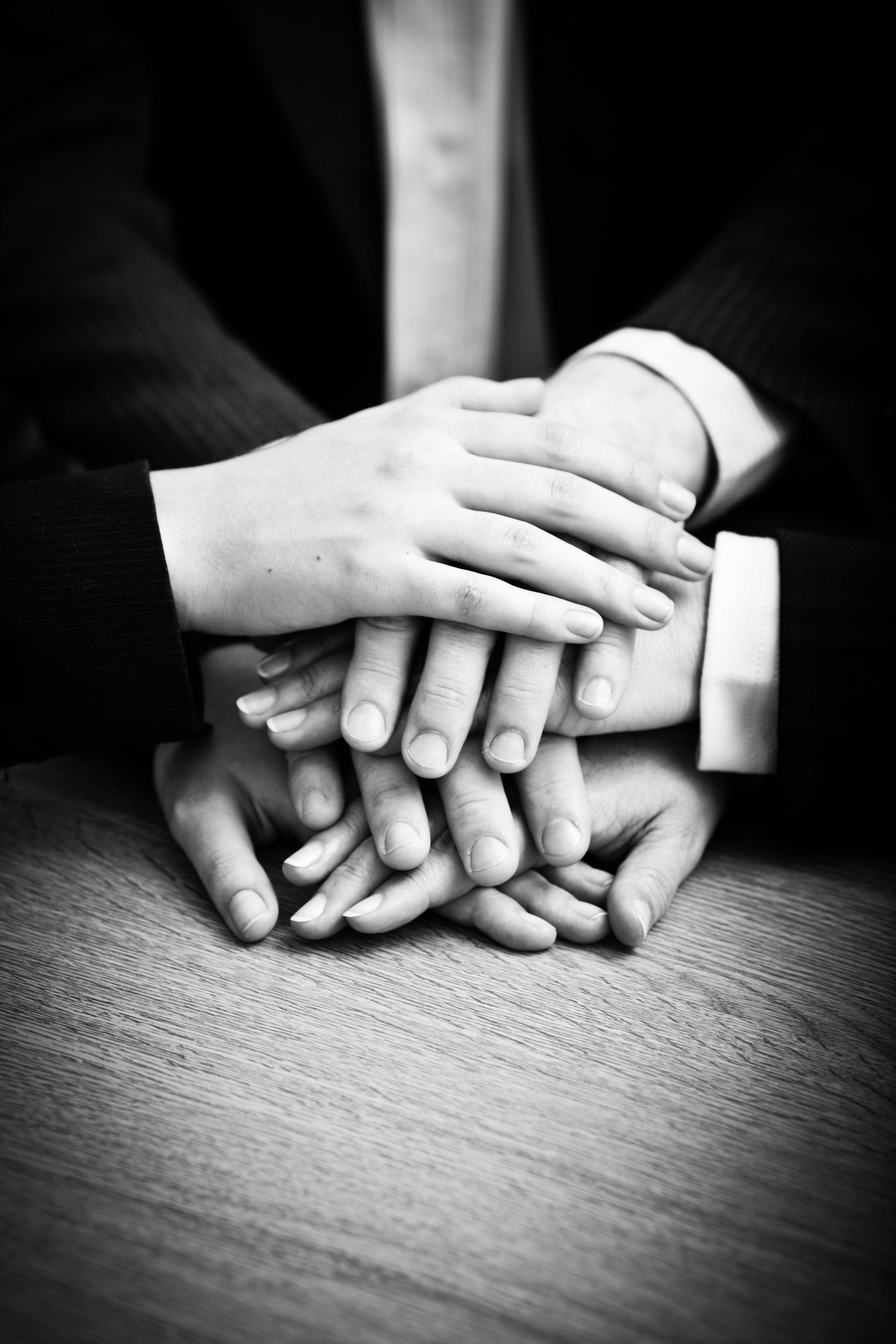 Image of business partners hands on top of each other symbolizing comp
